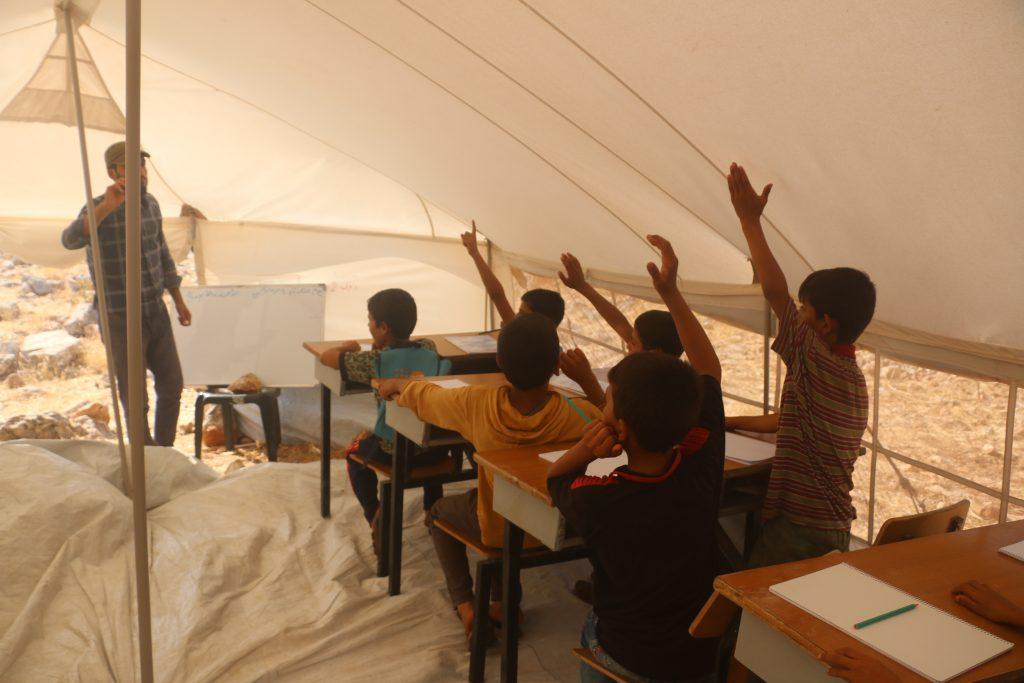 Niños levantan la mano en escuela