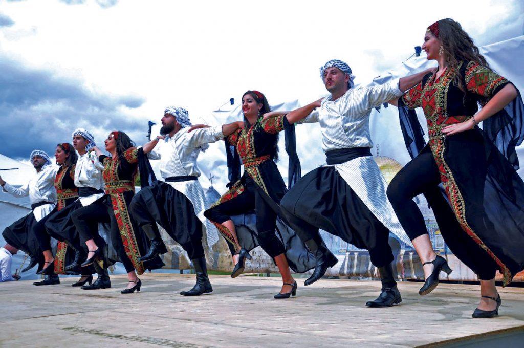 Mujeres y hombres bailando la danza de la dabke
